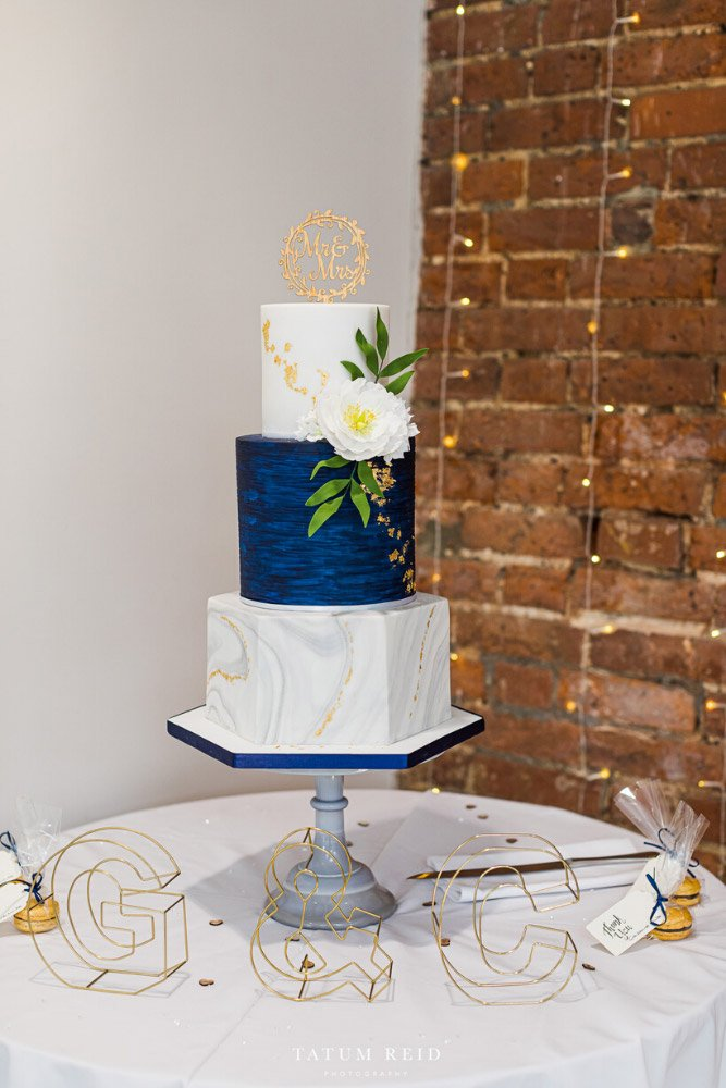 Grey marble hexagonal navy wedding cake with three tiers