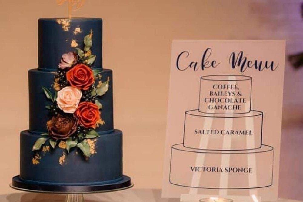 Navy and gold wedding cake with wedding cake menu